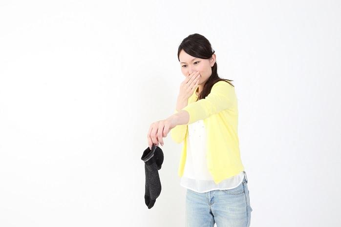 臭いのきつい靴下を持つ女性