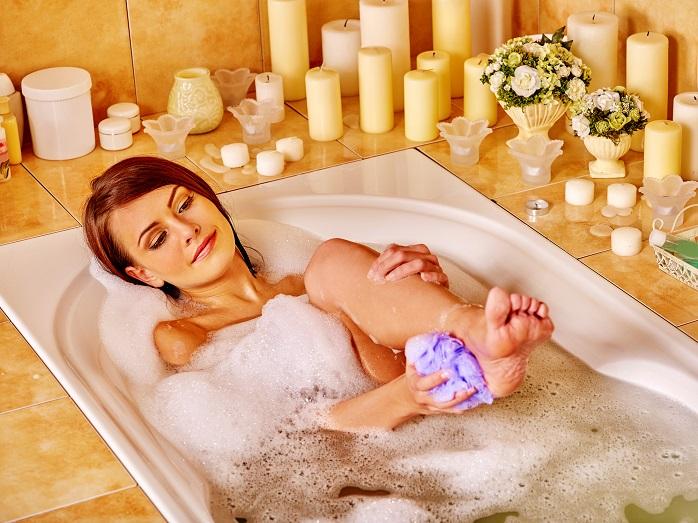 お風呂で丁寧に足を洗う女性