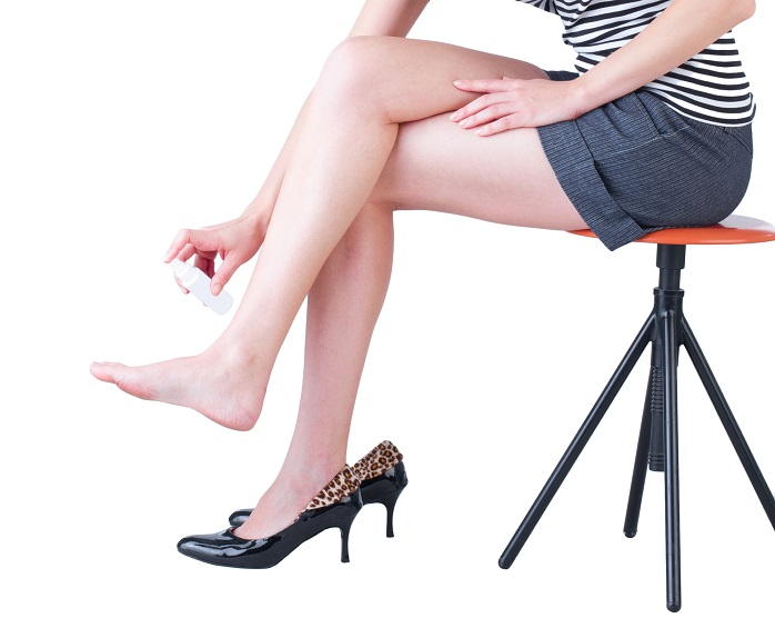 女性が足に消臭スプレーをしている