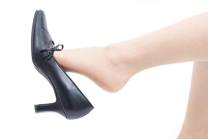 ハイヒールをつま先でぶらぶらしている女性の足