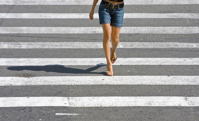 道路を警戒に歩いている女性