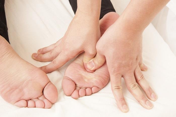 女性が足の裏を足つぼマッサージされている写真