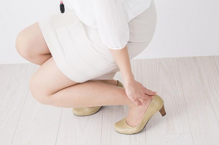 疲れた足をさすっている女性