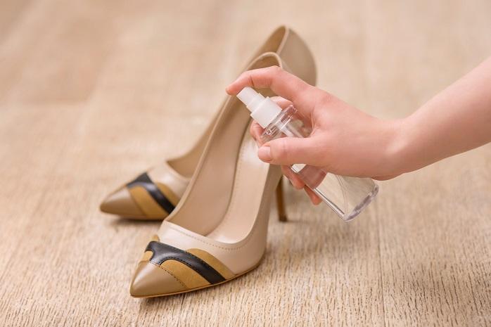 靴に消臭スプレーをしている